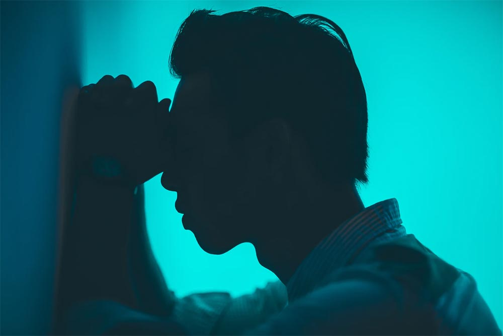 Silhouette of young man resting head on clasped hands against a wall wondering what treatment can ease his chronic pain