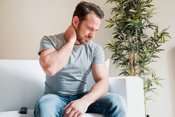 Man seated and grimacing as he rubs his neck which is in chronic pain - a Fibromyalgia symptom
